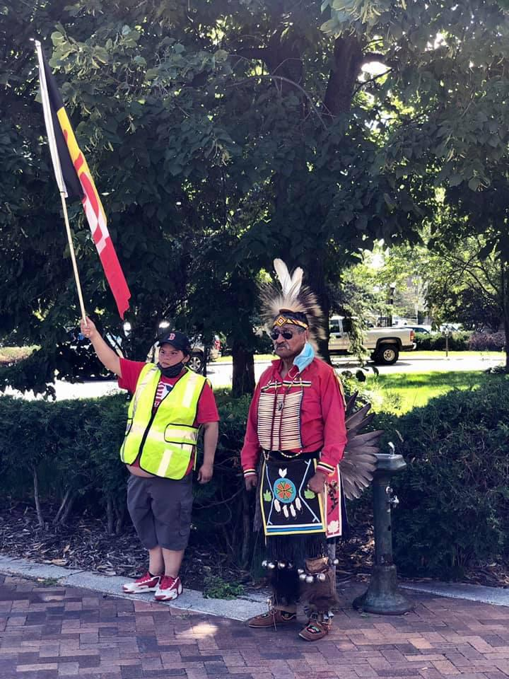 Caption: Medicine man Sid Perrault stands with his fellow marcher, Sage, at last Monday's event., Credit: Deb Holman. Used with permission