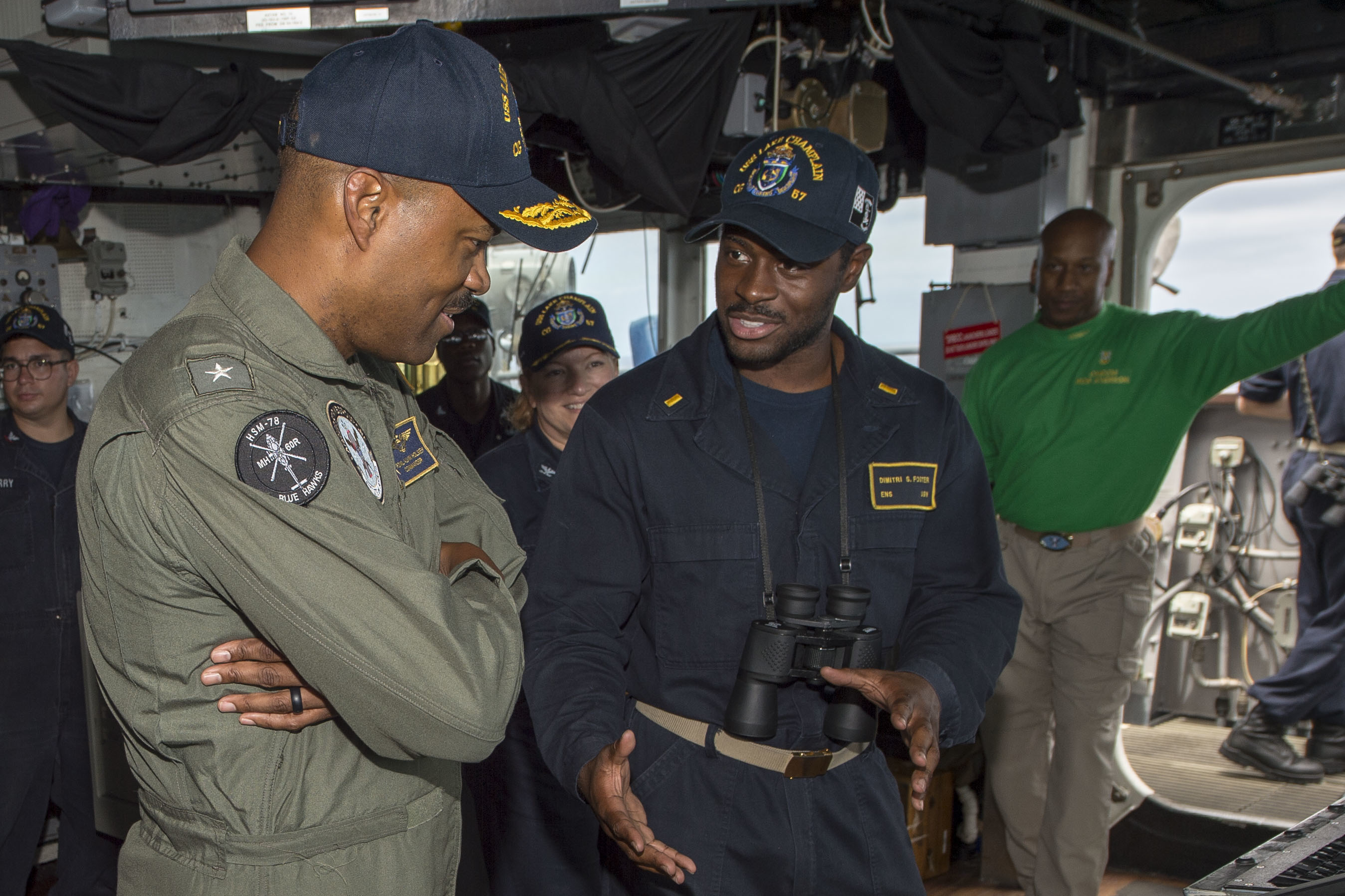 Caption: Rear Adm. Alvin Holsey (left) speaks with Ensign Dimitri Foster aboard the USS Lake Champlain in 2018. Holsey - one of the Navy's few Black admirals - heads the One Navy Task Force., Credit: Craig Z. Rodarte / U.S. Navy
