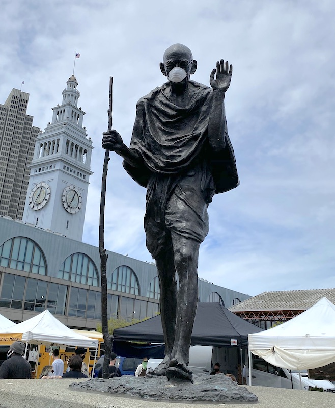 Caption: A masked statue of Gandhi in San Francisco's Ferry Plaza, Credit: Eric Wayne