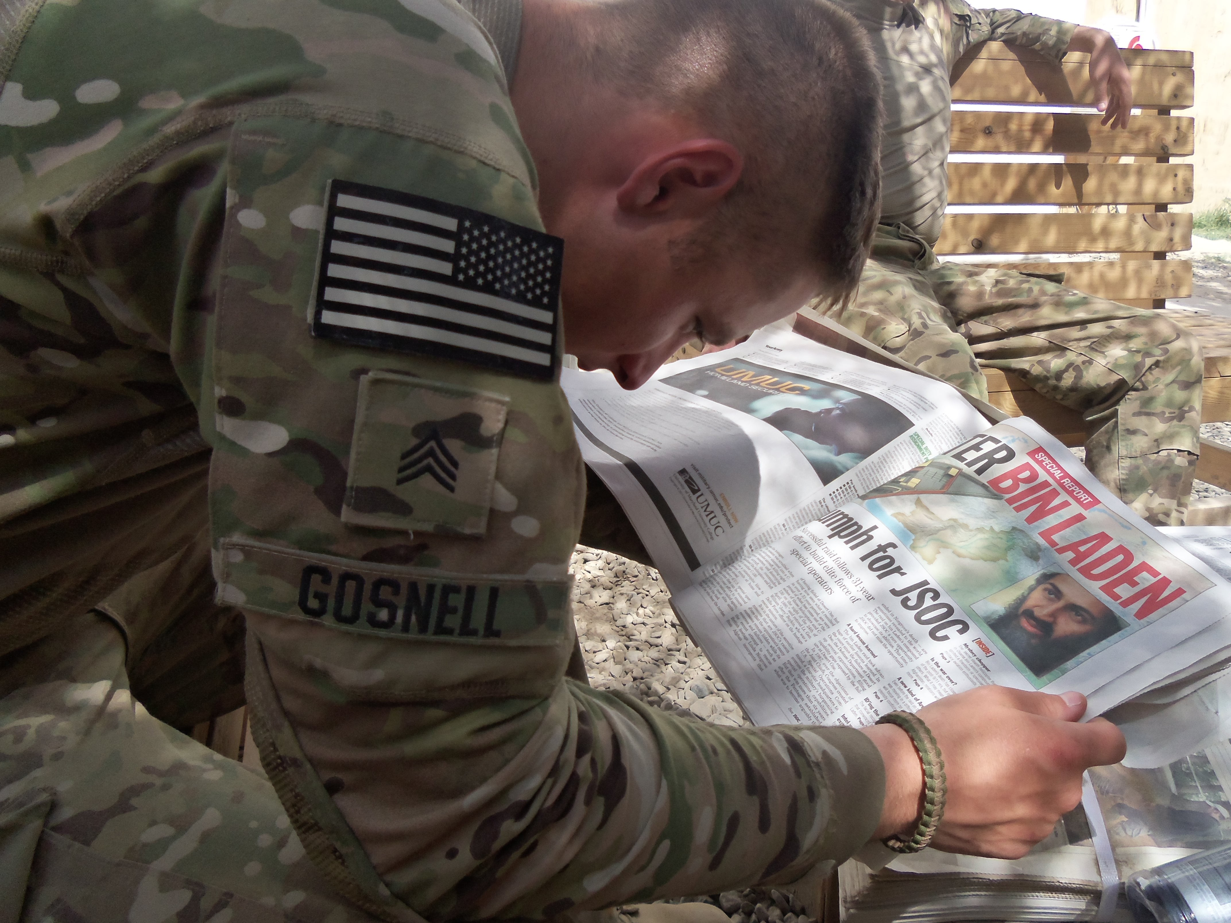 Caption: A soldier in Logar Province, Afghanistan reads about the capture of Osama Bin Laden in a 2011 issue of the Stars and Stripes., Credit: Christopher Hall / Georgia National Guard
