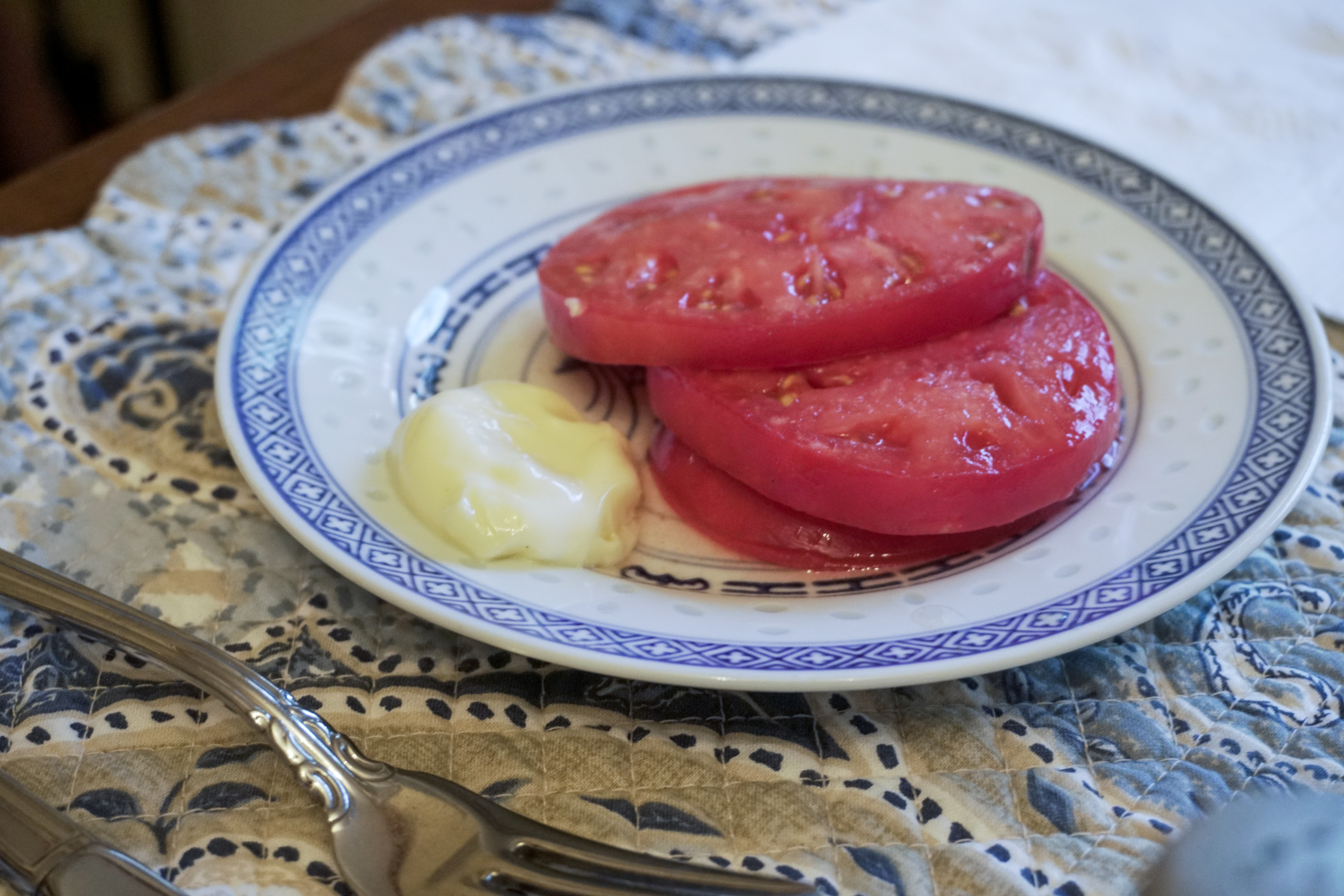 Caption: Mary Lou Estler slices up her family's heirloom mortgage lifter tomato. But there's a mystery with this tomato. Listen to the show to learn more., Credit: Zack Harold/ WVPB