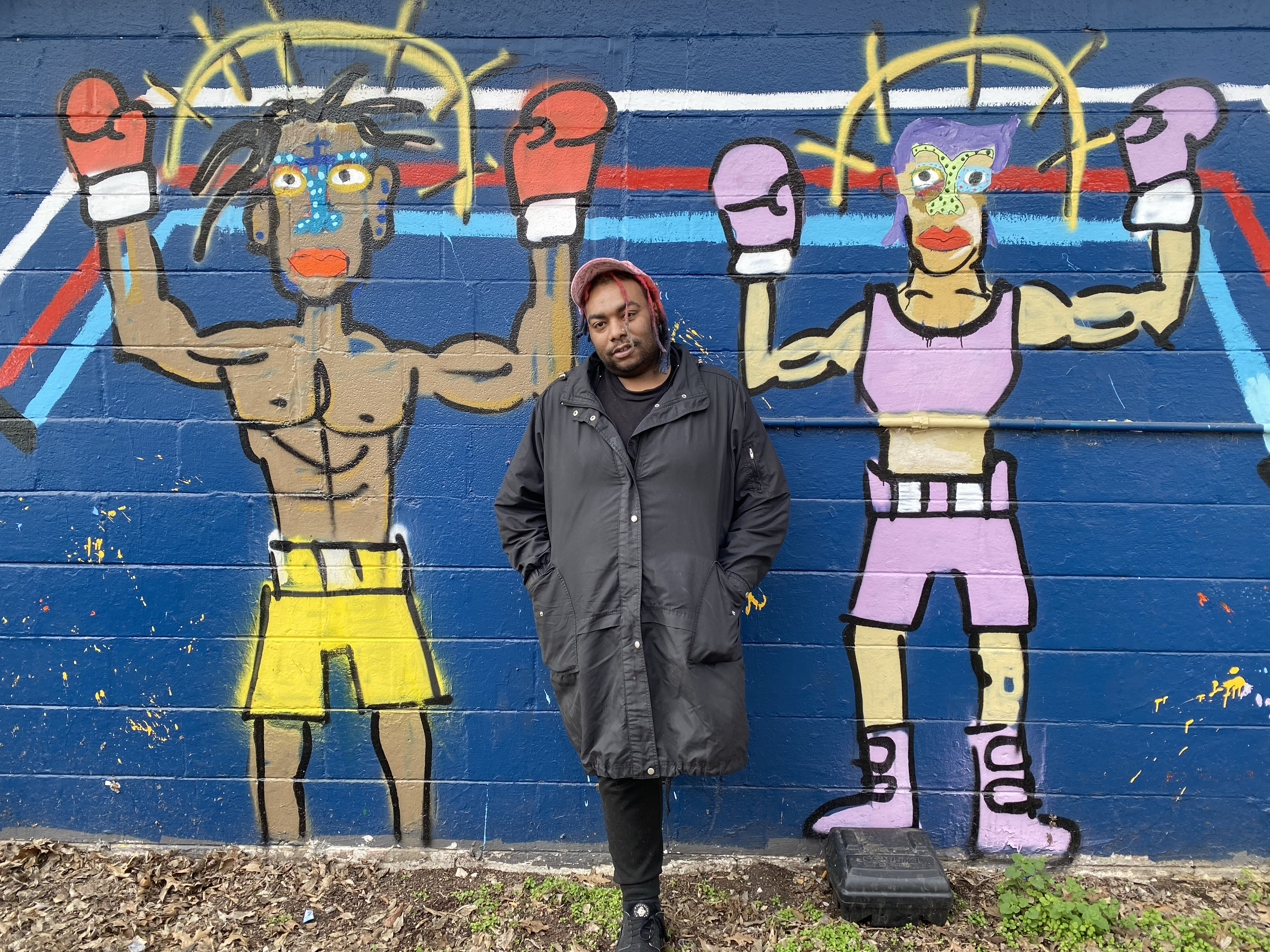 "Caption: Marlos E'van standing in front of his North Nashville mural, ""Fighters."" , Credit: Photo by Melissa Saenz Gordon"