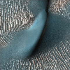 Caption: The High Resolution Imaging Science Experiment (HiRISE) camera aboard NASA's Mars Reconnaissance Orbiter captured these sand ripples and the large dune (at center) on Feb. 9, 2009. Color has been added to make textures easier to see., Credit: NASA/JPL-CALTECH