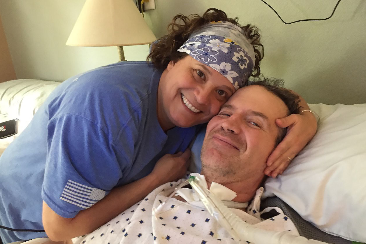 Caption: Lara Garey comforts her husband Tom in 2019. Tom served in the Air Force from 1989-1996 and was diagnosed with service related ALS in 2016.