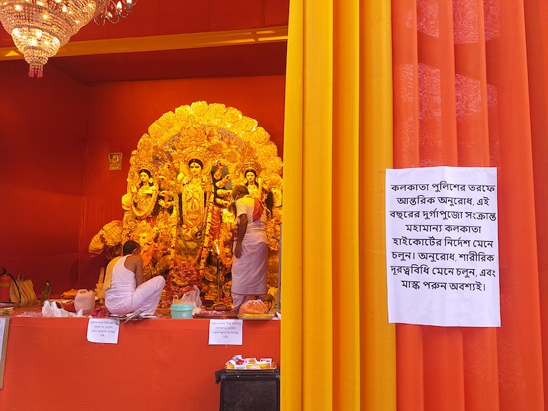 Caption: A Bengali sign that asks visitors to wear masks during the Durga Puja festival in Kolkata, Credit: Sandip Roy