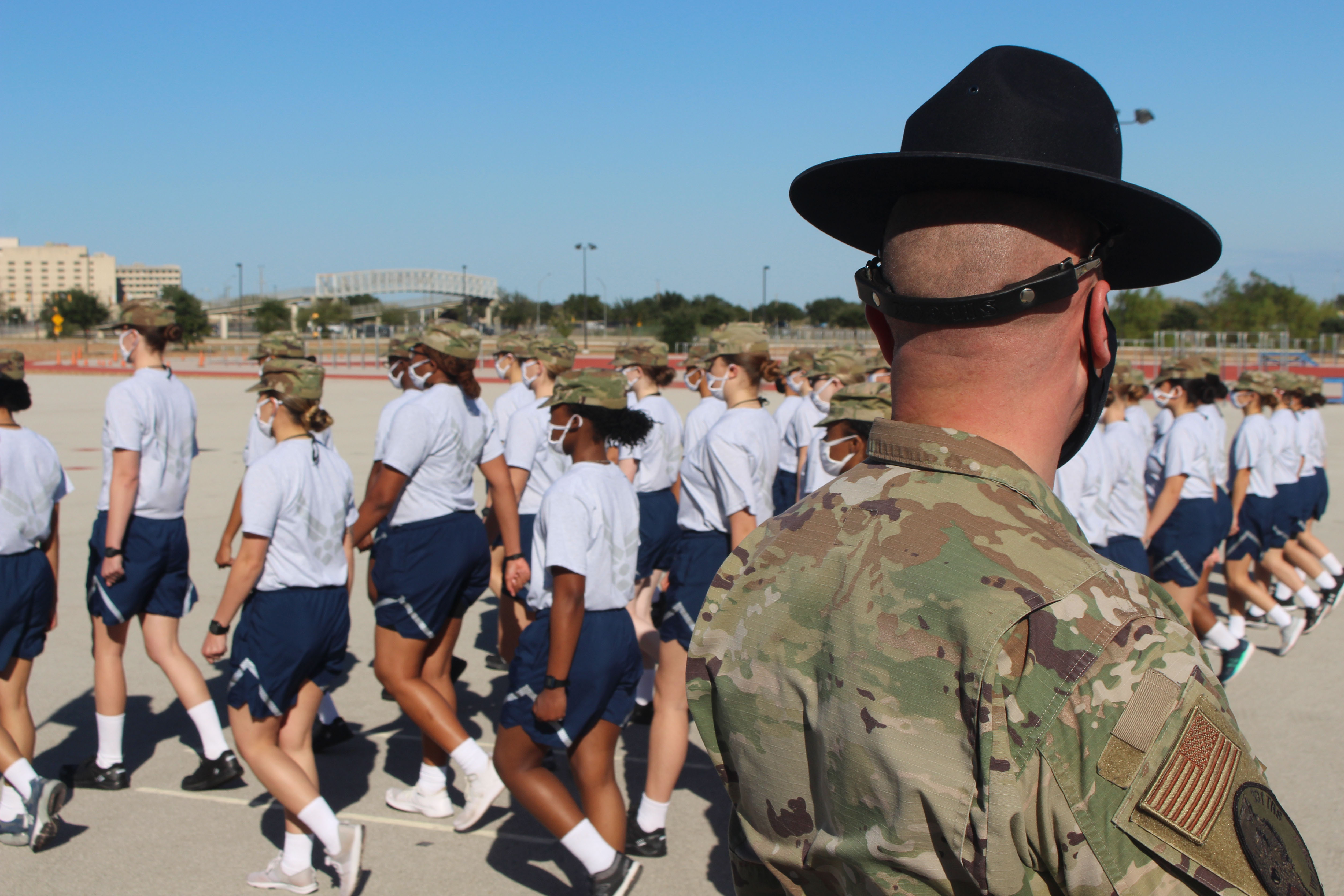 Caption: Trainees march in formation at Joint Base San Antonio-Lackland. The Air Force has restructured basic military training so that there is less travel time and fewer opportunities to practice drill., Credit: Carson Frame / American Homefront