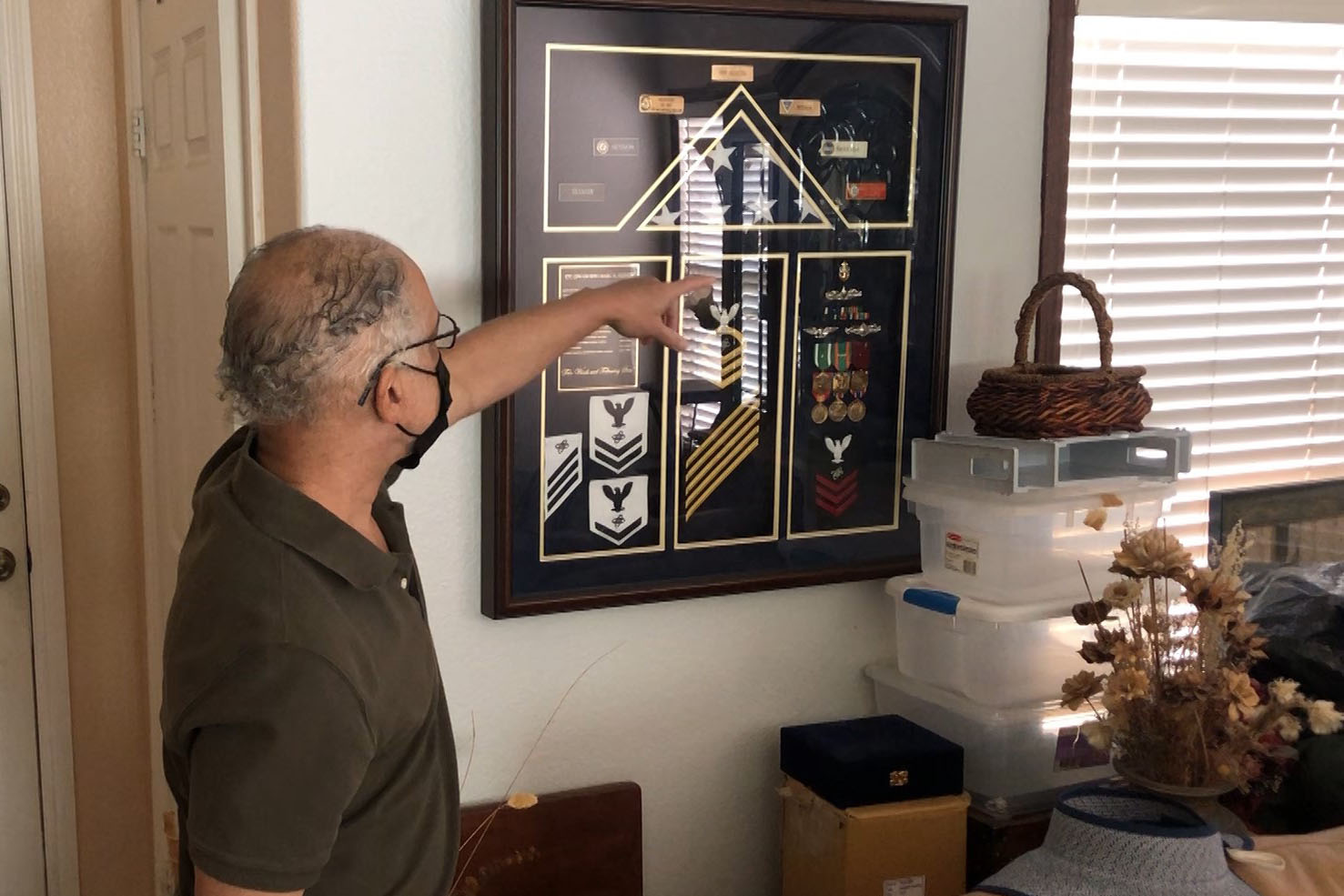 Caption: Veteran Marc Session points to some of his Navy mementos on display in his Chula Vista, California home., Credit: Steve Walsh / American Homefront