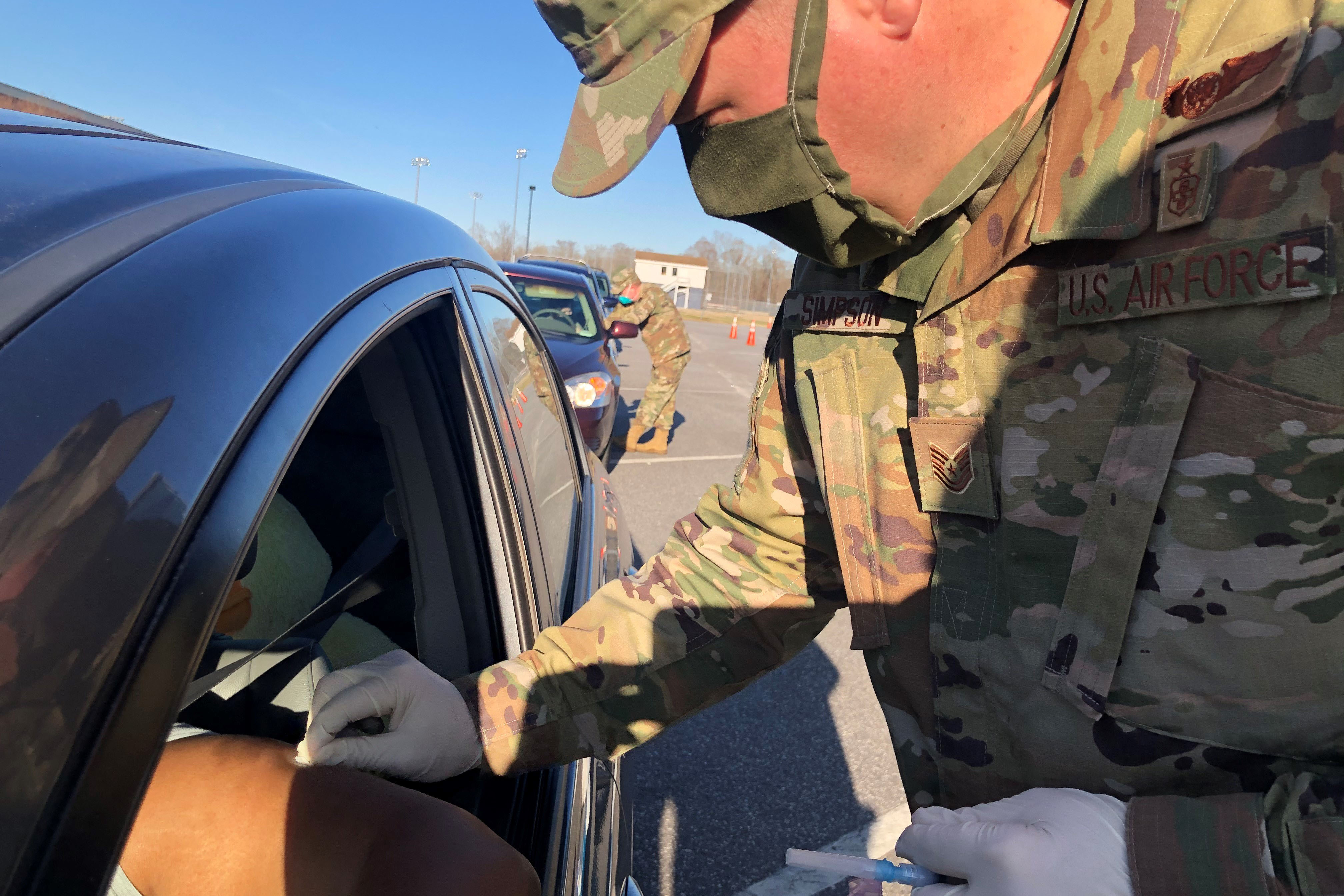 Caption: At a drive-through vaccination site in Elizabeth City, N.C., Tech Sgt. Steven Simpson of the North Carolina National Guard administers a COVID-19 vaccination as Maj. Hollis Guenther gives the next recipient instructions about the vaccine., Credit: Jay Price / American Homefront