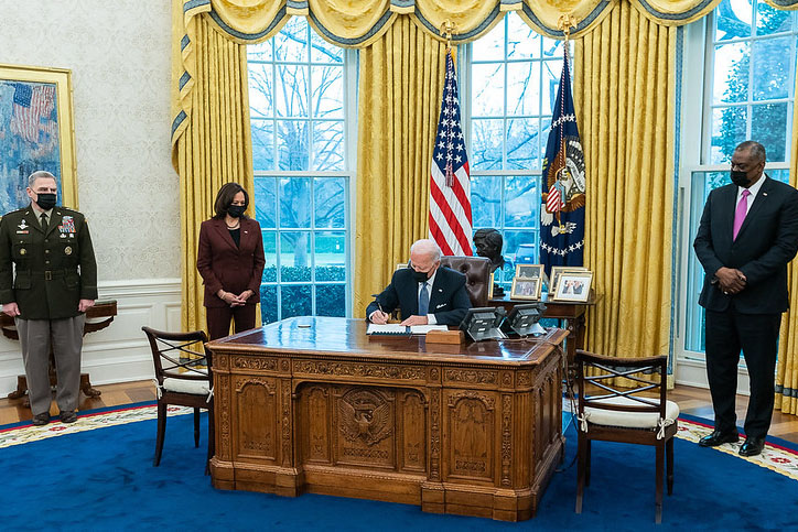 Caption: President Biden signs a Jan. 25 order repealing the military transgender ban, as Vice President Harris, Chairman of the Joint Chiefs Mark Milley (left), and Defense Secretary Llyod Austin watch., Credit: Adam Schultz / White House photo