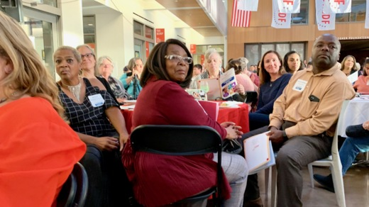 Caption: Geraldine Robinson, center, and one of her sons, right, wait for her to be honored for her advocacy by the Disability Rights Education & Defense Fund in September 2019