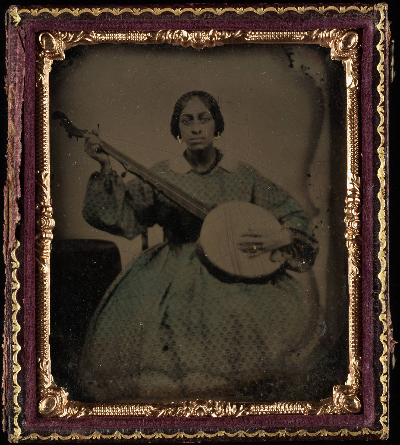 Caption: Portrait of a young black woman, seated, holding nine string banjo, Credit: Yale Collection of American Literature, Beinecke Rare Book and Manuscript Library