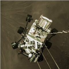 Caption: The Mars 2020 rover Perseverance imaged as it is lowered to the Red Planet's surface by the sky crane., Credit: NASA/JPL-Caltech