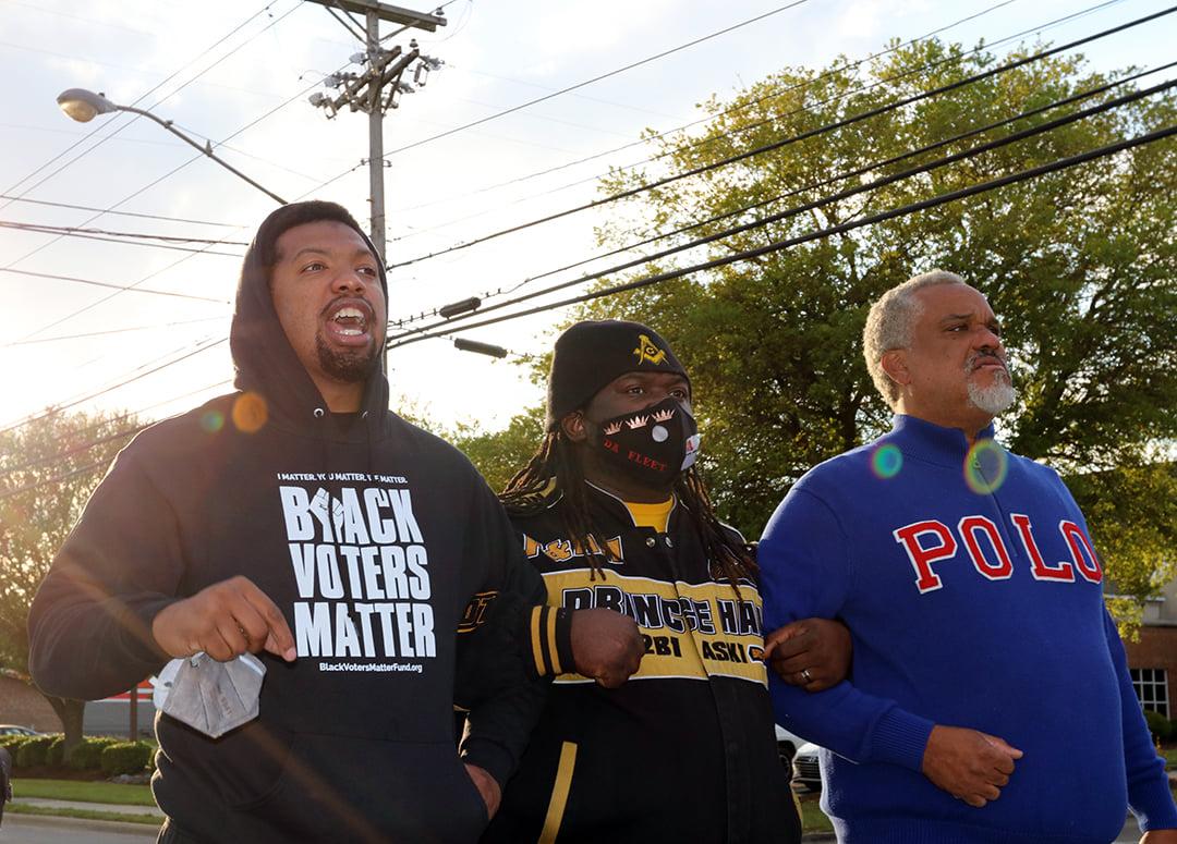 Caption: Activist and community organizer Quentin Jackson, left, marches in Elizabeth City.