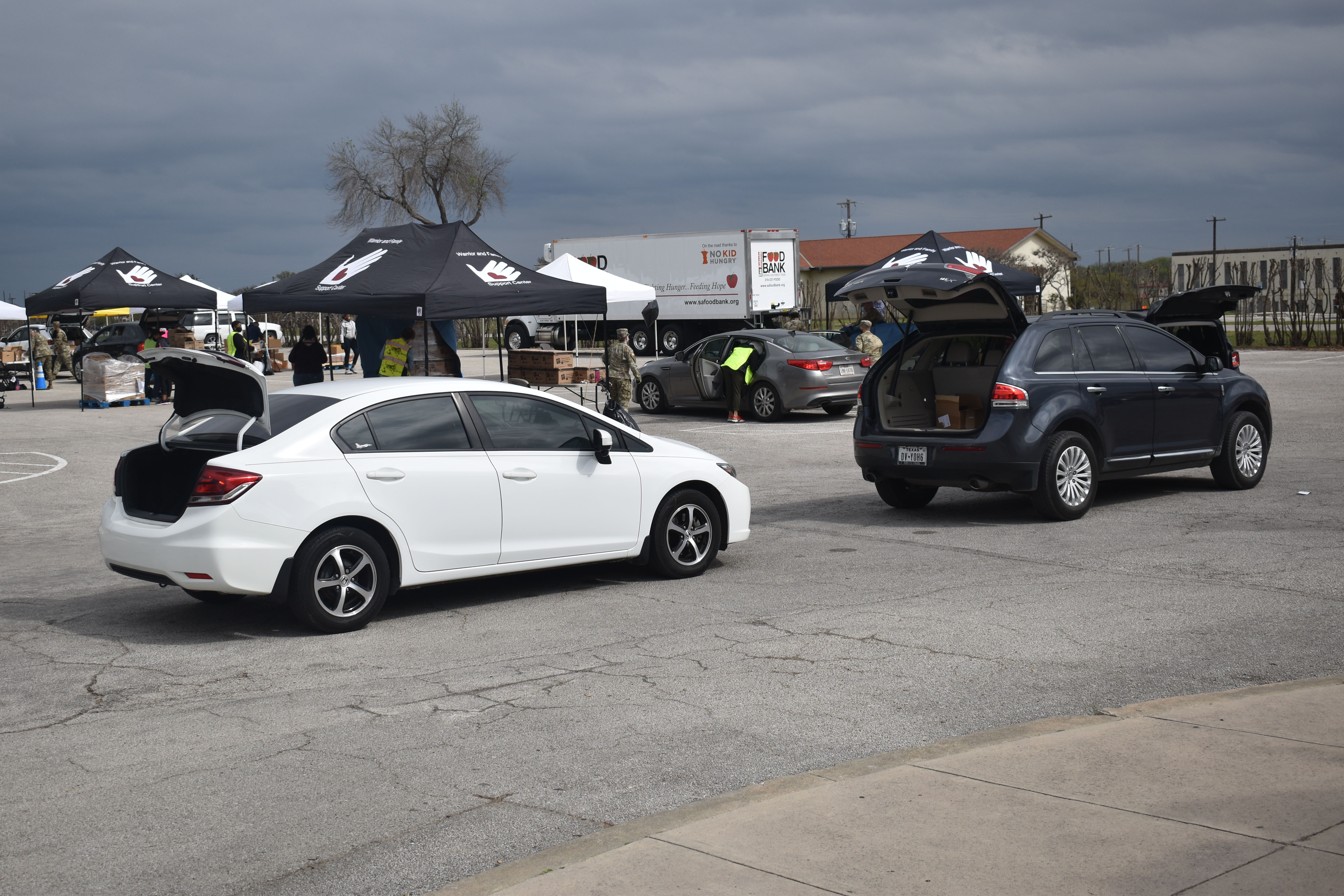 Caption: Cars line up at a March food distribution event at Fort Sam Houston in San Antonio., Credit: Carson Frame / American Homefront