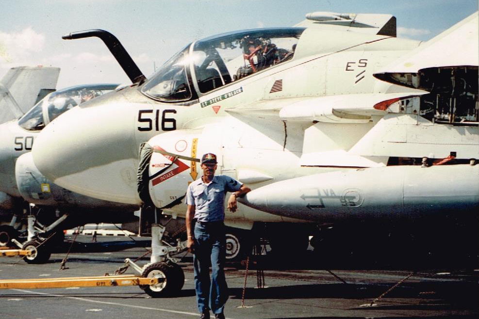 Caption: Former Navy sailor Louis Miller stands on the deck of the USS Enterprise aircraft carrier. Miller was kicked out of the Navy in 1992 for being gay., Credit: Courtesy Louis Miller