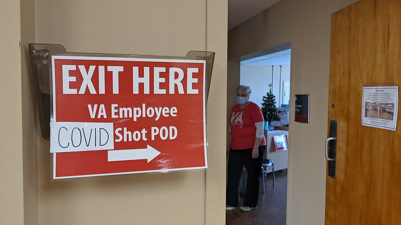 Caption: Employees at the VA Medical Center in Grand Island, Nebraska take part in a December 2020 employee vaccination event. The VA now is ordering more than 100,000 of its health care workers to get vaccines by mid-September or risk losing their jobs., Credit: A Nebraska-Western Iowa Health Care System