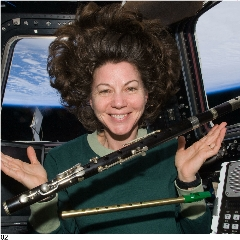Caption: Astronaut Cady Coleman, ISS-27 flight engineer, looks over two of four flutes brought with her to the International Space Station in her small allotment of personal items. She is in the Cupola., Credit: NASA
