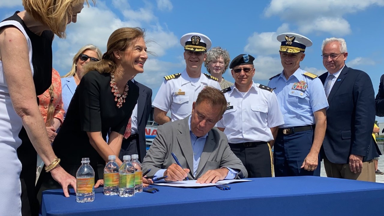 Caption: In an August ceremony, Connecticut Gov. Ned Lamont signs a law that makes it easier for military spouses to get professional licenses. The bill signing ceremony took place at Naval Submarine Base New London in Connecticut., Credit: Office of Gov. Ned Lamont