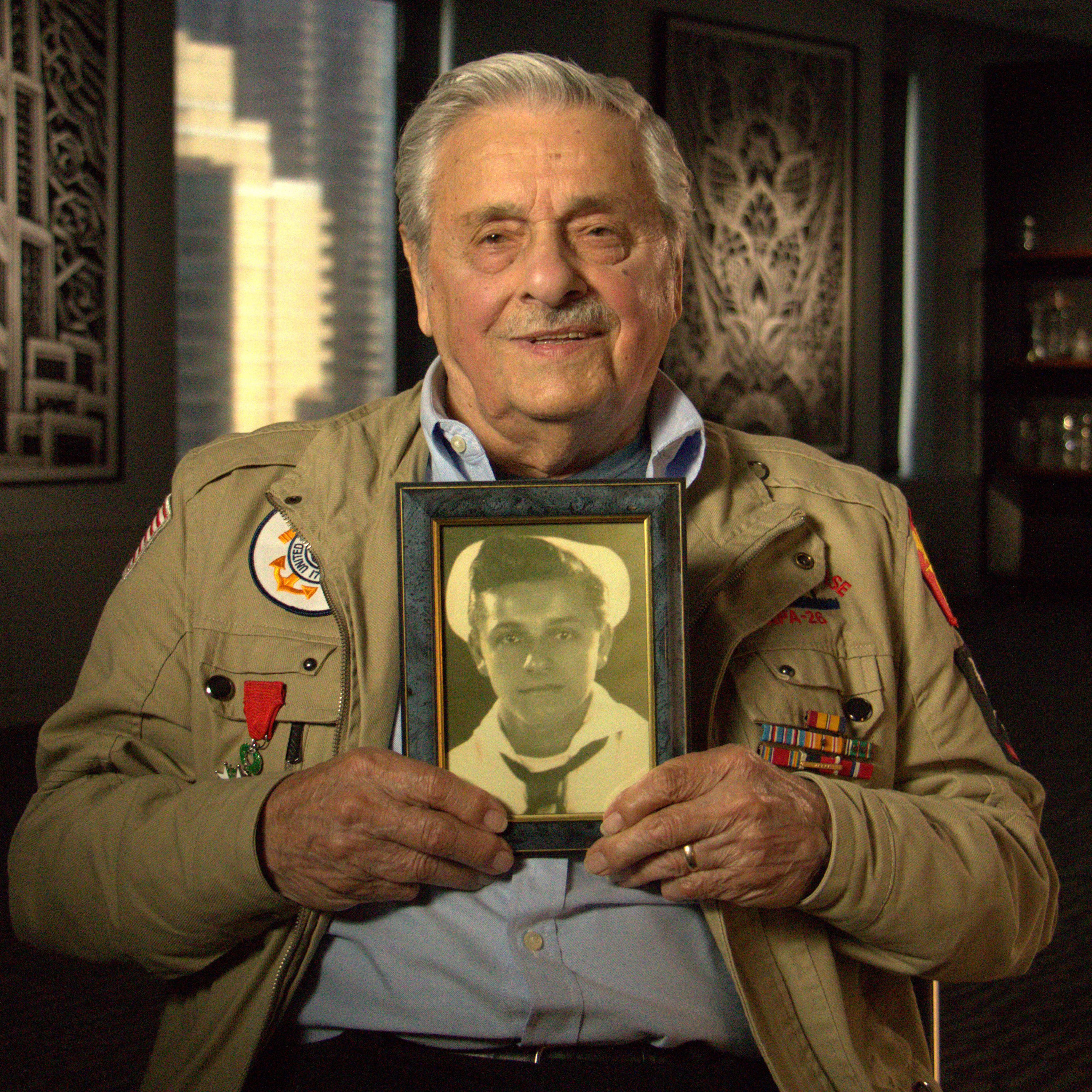Caption: Frank DeVita, veteran of the U.S. Coast Guard, holds a picture of himself in uniform when he served in World War II., Credit: Amanda Lalezarian
