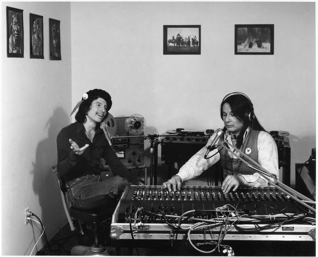 """Caption: Fred Veilleux, Ojibwe composer and musician, as he talks with Gary Fife in the sound studio of Migizi's """"First Person Radio"""" at 2300 Cedar Ave. S., Minneapolis; 1983, , Credit: Photograph by Randy Croce, courtesy of the Minnesota Historical Society"""