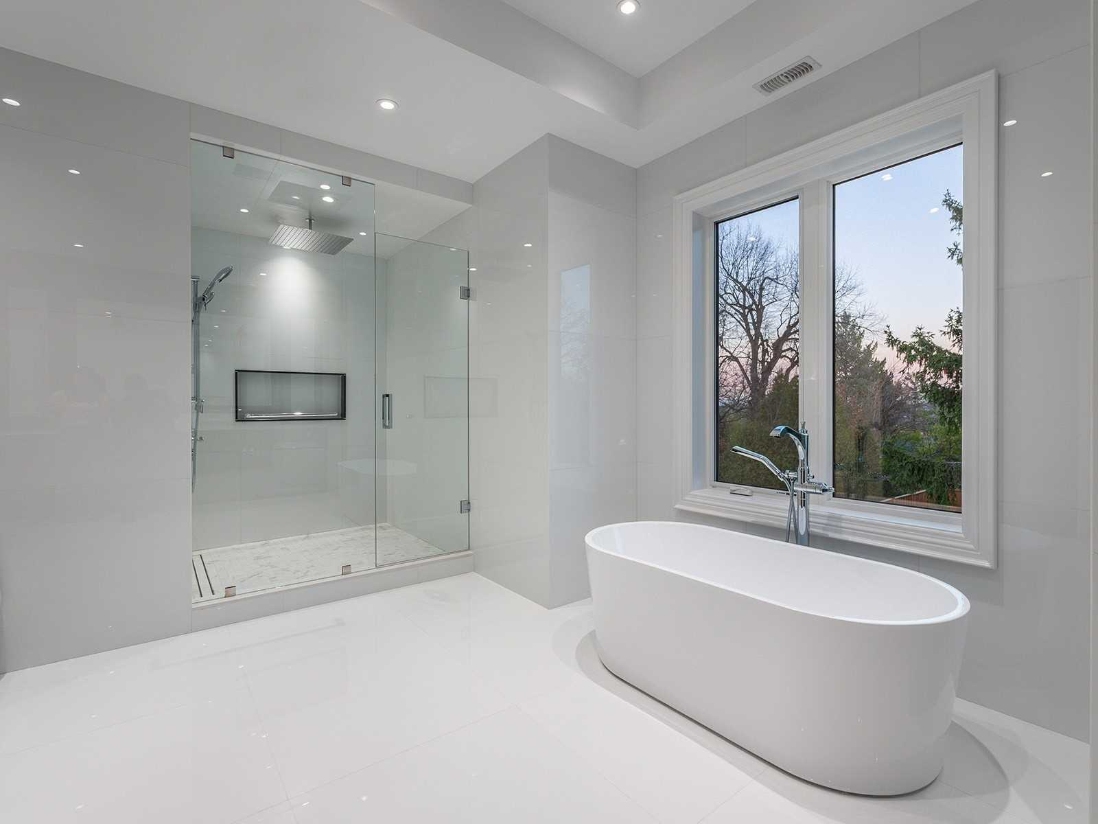 white-clad bathroom with walk-in shower and freestanding tub inside a luxury ontario home at 11 Whitman Street