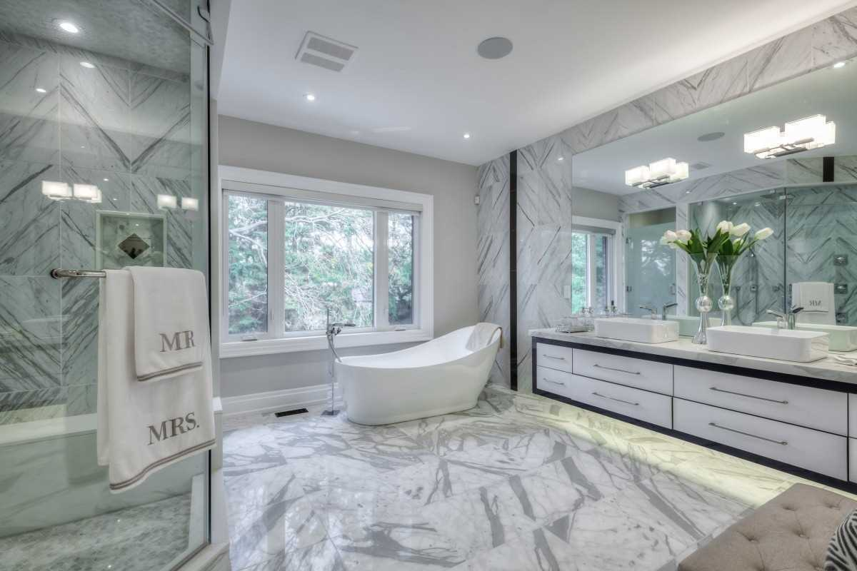 luxurious white marble bathroom with freestanding soaking tub inside the toronto home at 16 Beaverhall Drive