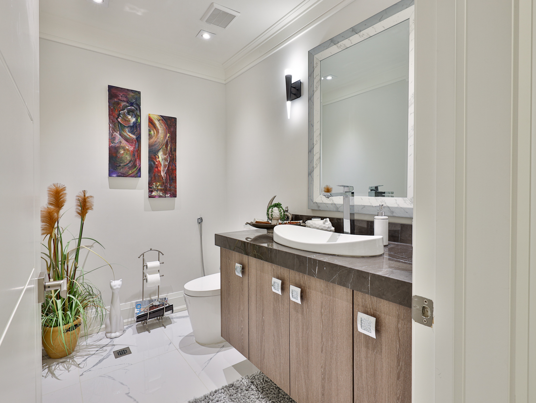black modern sconce brightens a bathroom inside a luxurious ontario home located at 7 Albion Close