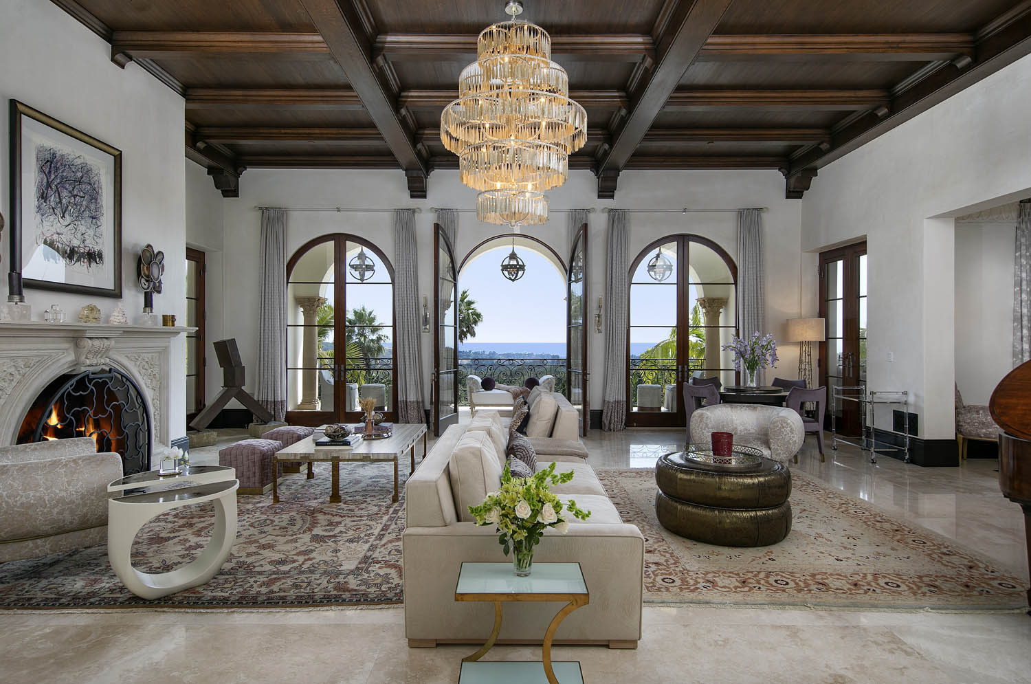 formal living room with fireplace, beamed ceilings and arched windows centered on the ocean