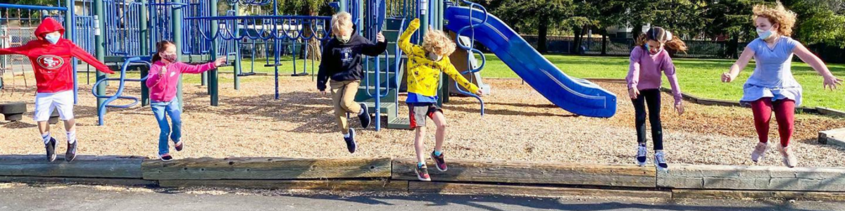 Students wearing masks jumping with playground in background