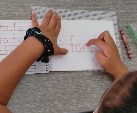Student tracing letters with their finger