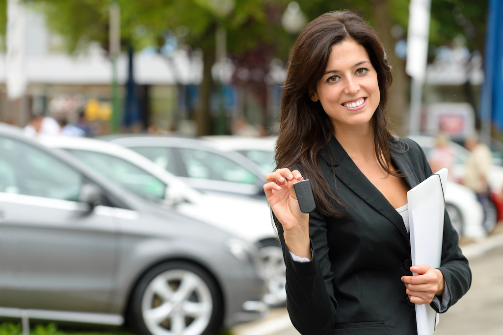 Female car seller holding car keys. Caucasian saleswoman in luxury vehicle trade fair. Auto rental or sales concept.