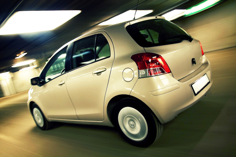 Rear view of compact hatchback driving fast in parking house