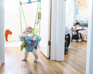 A baby girl standing in a baby bouncer hanging in a doorway.