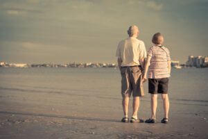 senior couple holding hands at the beach