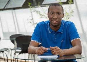 homem de camisa azul segurando caneta parecendo confiante