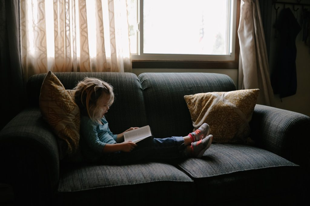 image of child reading a book on a couch