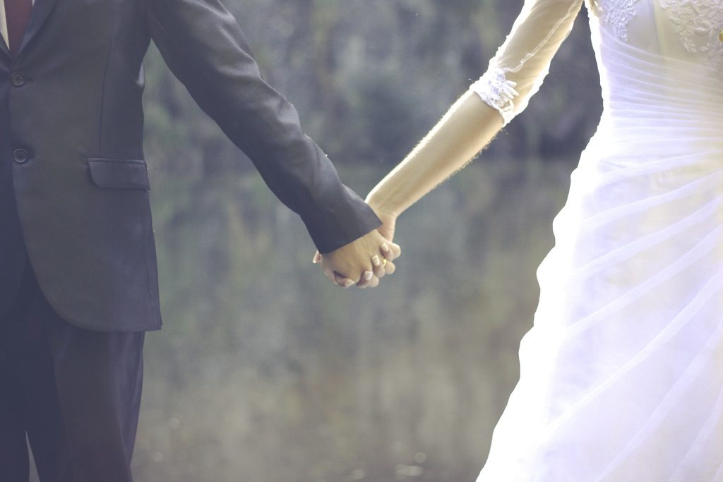 image of bride and groom holding hands