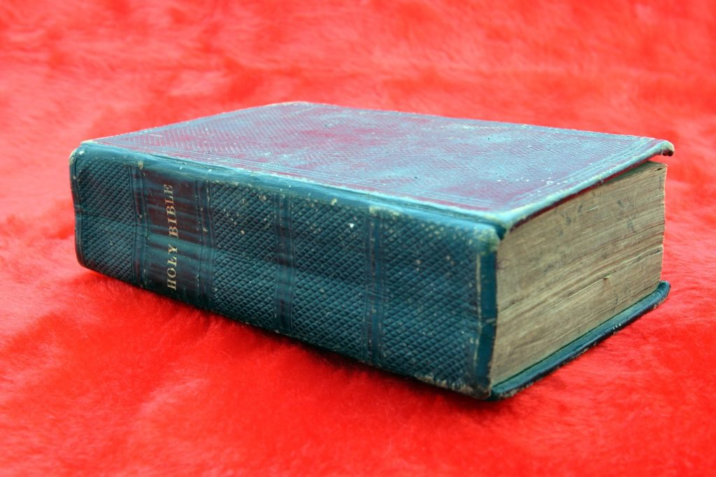 image of bible with blue cover on red tablecloth