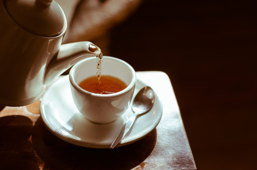image of tea being poured into white cup