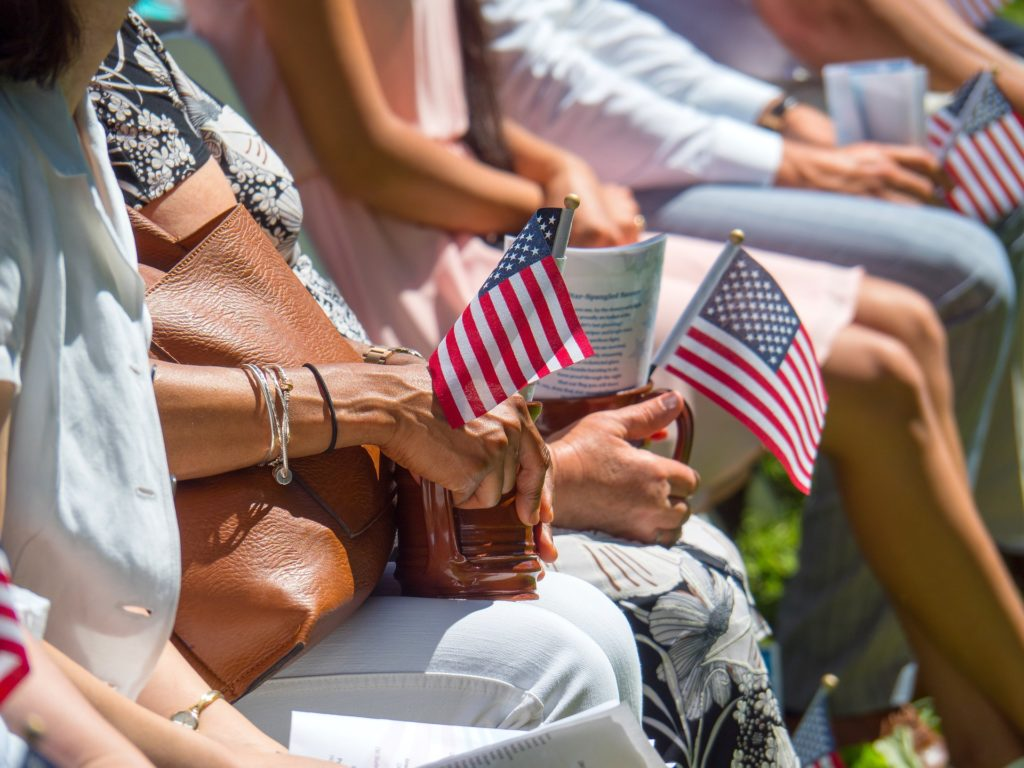close up of people's hands holding small American flags