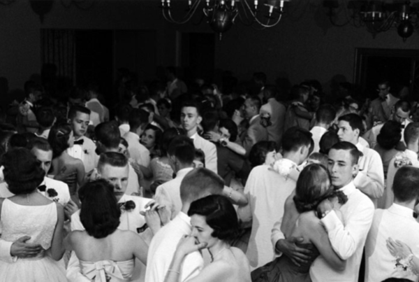 black and white photograph of a 1950s prom; everyone in the photo is white