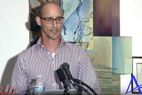 Photograph of Kevin Timpe talking in front of abstract art. He's wearing a lovely plaid shirt. Bottle water and two microphones are visible in front of him.