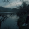 a still from the video, featuring a man in a red hoody sitting on the ground by a lake