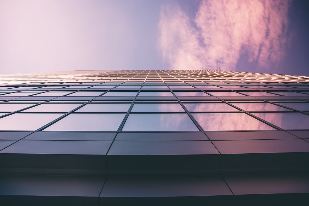 low angle photography of glass window high-rise building under white and blue cloudy skies