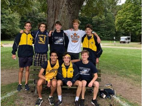 """The Varsity Team takes a picture on """"Don's"""" Bench.  This bench is where Coach Hasenstein's Dad loved to cheer the runners on from at Detweiller Park in Peoria. Don's voice and spirit will always be there as Titan runners pass by!"""