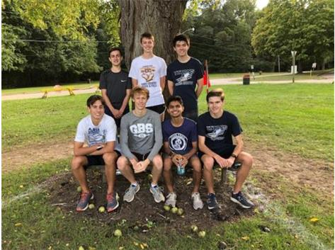 "The Varsity Team takes a picture on ""Don's"" Bench.  This bench is where Coach Hasenstein's Dad loved to cheer the runners on from at Detweiller Park in Peoria. Don's voice and spirit will always be there as Titan runners pass by!"