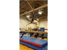 Sophomore Cassie Corbes competing her split jump 3/4 on beam.