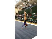 Frehsmen Athena Xidis performing her handstand double paro during her floor routine.