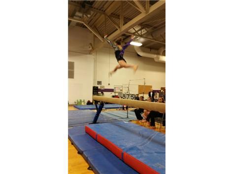 Freshman Athena Xidis splitting high above the beam.