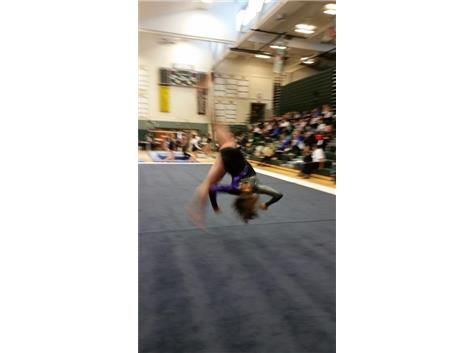 Sophomore Kyra VanDoren performing an aerial on floor during her routine.